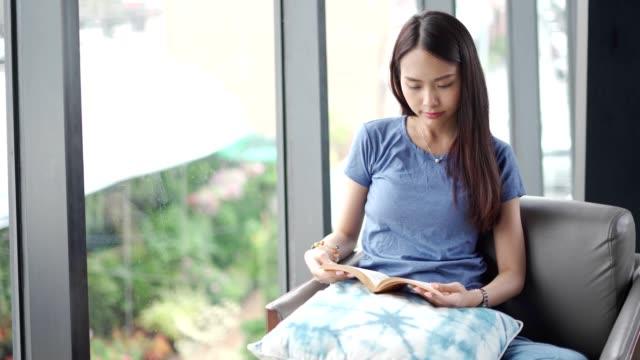 vídeos de stock e filmes b-roll de a young lady is reading book sitting on the windowsill - peitoril de janela