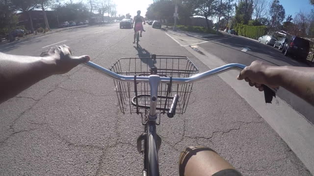 pov of a young man and woman riding bikes together. - handlebar stock videos & royalty-free footage