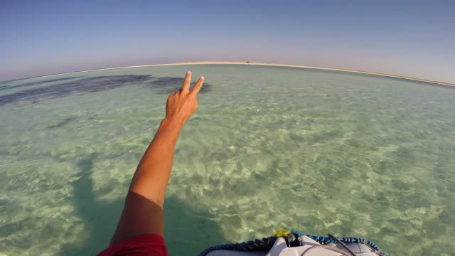 stockvideo's en b-roll-footage met pov of a young man  doing the peace sign while boating in a bay in egypt. - filmed in soma bay, egypt, africa - vredesteken handgebaar