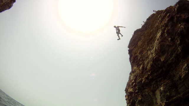vidéos et rushes de pov of a young man jumping off a cliff in malta. - slow motion - model released - hd - cliff