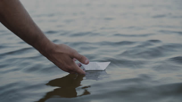 vidéos et rushes de cu of a young man placing a love letter in the shape of a boat in the ocean - pushing