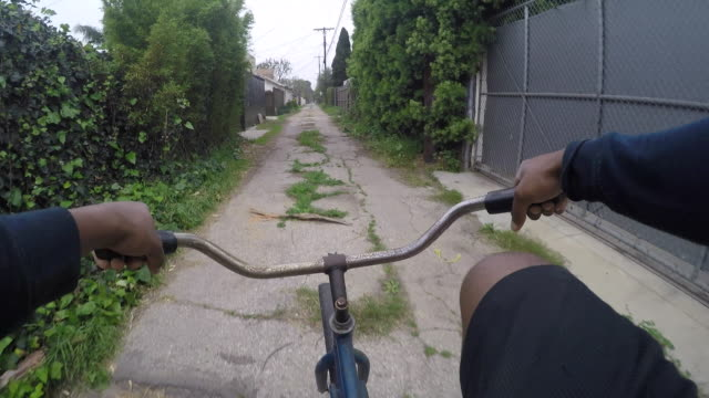 POV of a young man riding his bike in a neighborhood alley.