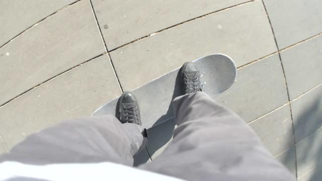 vidéos et rushes de pov of a young man riding his skateboard in a town square. - slow motion - caméra portable