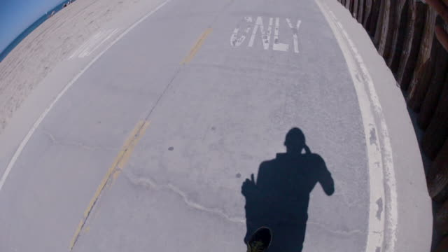 pov of a young man running on a bike path at the beach. - goodsportvideo stock videos and b-roll footage