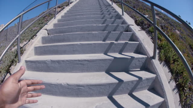POV of a young man running stairs at the beach.
