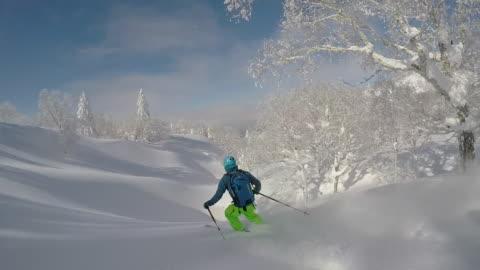 vidéos et rushes de pov of a young man skier skiing on a snow covered mountain. - seulement des jeunes hommes