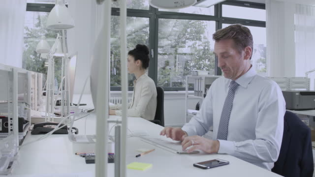 a young, professional business person works at his desk in a creative, stylish office setting - elektrische lampe stock-videos und b-roll-filmmaterial