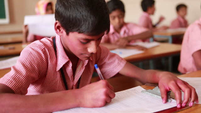 cu of a young schoolboy that is sitting at a desk while he is entering his name in an attendance list on march 28 2013 in bijapur india his face is... - christian ender stock-videos und b-roll-filmmaterial