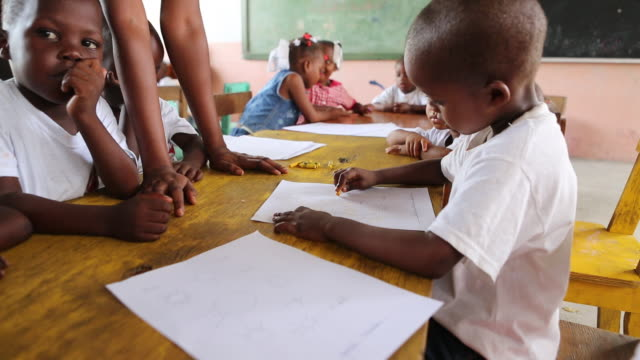ms of a young schoolboy who is drawing a sun with a wax crayon in a classroom of a nursery school in portauprince haiti while a teacher is helping... - crayon stock videos and b-roll footage
