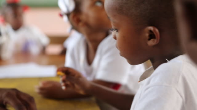 of a young schoolboy who is drawing a sun with a wax crayon in a classroom of a nursery school in port-au-prince, haiti while a teacher is helping... - crayon stock videos & royalty-free footage