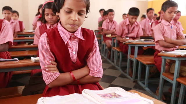 cu of a young schoolgirl that is sitting at a desk with her arms crossed while she is reading in a book her name on march 28 2013 in bijapur india... - christian ender stock-videos und b-roll-filmmaterial
