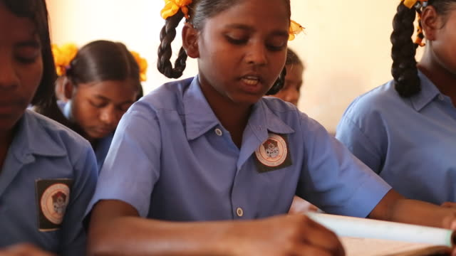 CU of a young schoolgirl who is reading a book at her desk during class in a school in the village Satia a small settlement 300 Kilometer from...