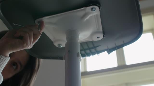 diy. cu einer jungen frau montage flache pack möbel mit einem schraubendreher. hausverbesserung und reparatur. montage eines bürostuhls. - genderblend stock-videos und b-roll-filmmaterial