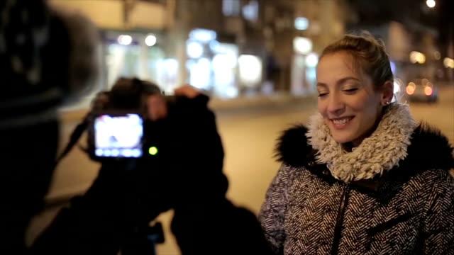 eine junge Frau gibt ein Interview auf der Straße