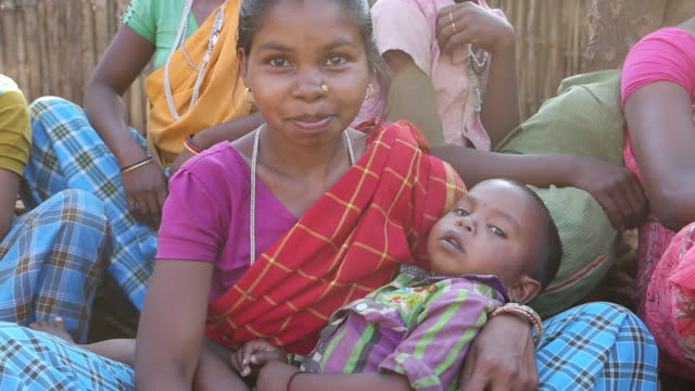 CU of a young woman in a colourful sari sitting on a bench while she is holding a baby in a rural area of the village Satia a small settlement 300...