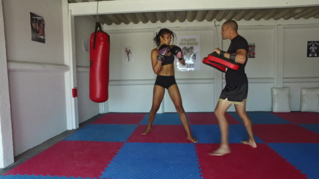 a young woman training for combat sports. - muay thai stock videos and b-roll footage