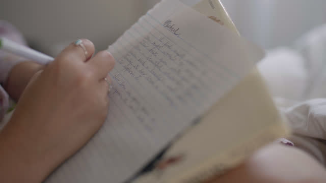 cu of a young woman's hand writing a handwritten love letter in bed - 手書き文字点の映像素材/bロール