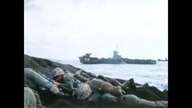 vidéos et rushes de aamphibious tank makes its way inland / soldier smoking / soldiers crouched on beach hiding / soldiers and their supplies littered along the beach... - véhicule amphibie