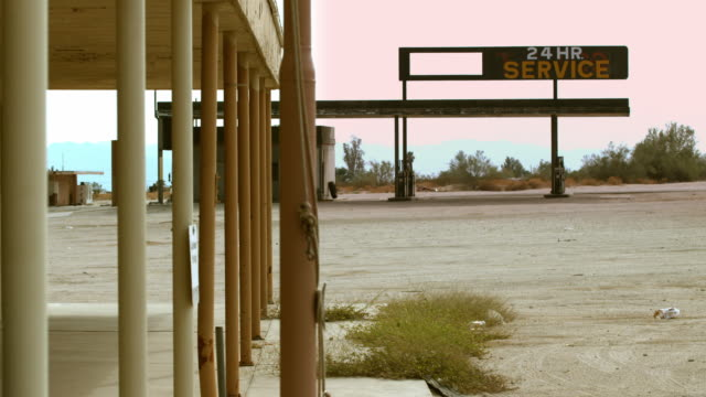 ws abandoned 24 hour gas station in remote area and dangling flag pole chain in front of abandoned building / desert center, california, usa  - ガソリンスタンド点の映像素材/bロール