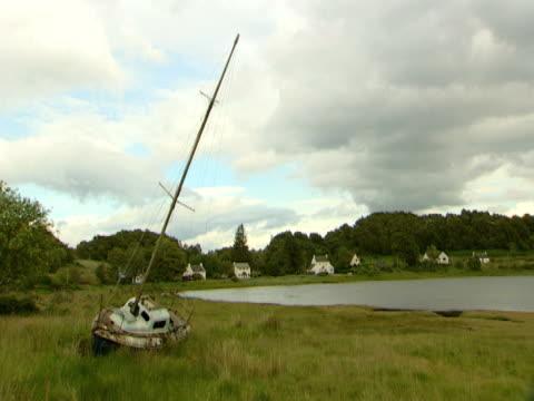 vídeos de stock e filmes b-roll de abandoned boat by lake, calm, woodland, scrub, picture postcard - ilha mull