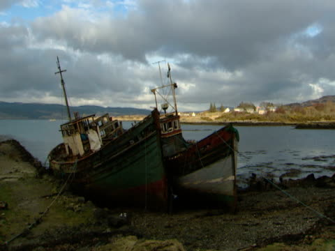 vidéos et rushes de abandoned boat on beach, calm  , woodland islands in distance, peaceful, tranquil, loss of industry - mull