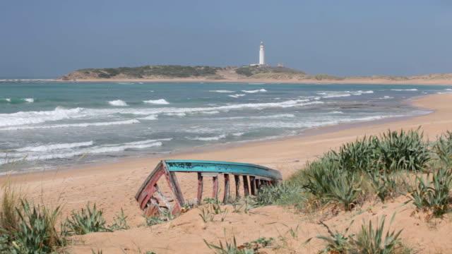 vídeos de stock e filmes b-roll de abandoned boat on the beach - farol estrutura construída