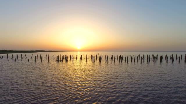 日の出、空撮で湖に放棄された破壊された木製の桟橋 - クワッドコプター点の映像素材/bロール