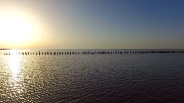 Abandoned destroyed wooden pier on lake at sunset, aerial video