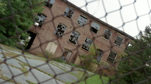 vidéos et rushes de ms, canted, abandoned factory building seen through chain link fence, beacon, new york, usa - délabré