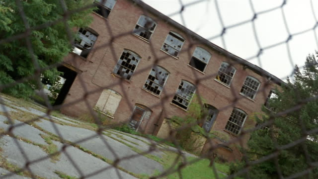 ms, canted, abandoned factory building seen through chain link fence, beacon, new york, usa - bad condition stock videos & royalty-free footage