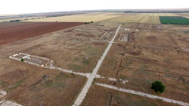 aerial: abandoned farm buildings and broken concrete road - calcestruzzo video stock e b–roll