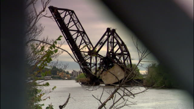 abandoned nx bridge bascule drawbridge in raised position over passaic river smokestack trees buildings bg railings partially obstructing view fg... - bascule bridge stock videos and b-roll footage