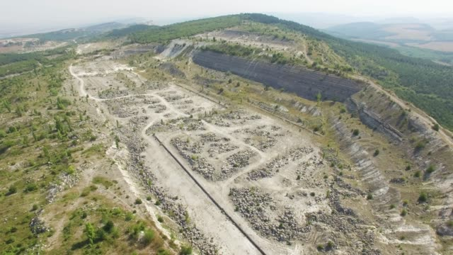 AERIAL: Abandoned old stone quarry in mountain