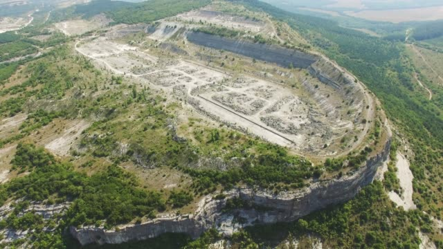 aerial: abandoned old stone quarry in mountain - quarry stock videos and b-roll footage