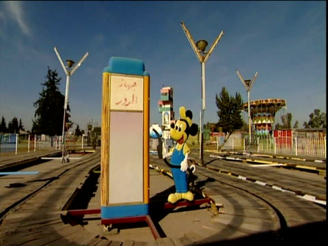 Abandoned playground with funfair rides and portrait of Saddam Hussein Mosul; 2002