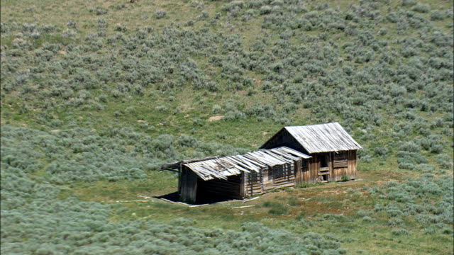 abandoned ranch on grass plain  - aerial view - wyoming,  sublette county,  helicopter filming,  aerial video,  cineflex,  establishing shot,  united states - wyoming ranch stock videos & royalty-free footage