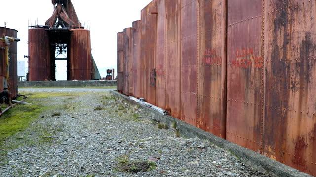abandoned rusty whaling station buildings in snowfall - 大西洋諸島点の映像素材/bロール