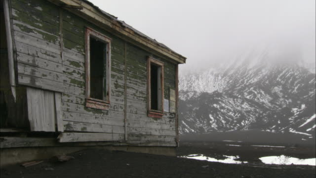 MS, Abandoned scientific station, snow capped mountains covered with fog in background, Deception Island, Antarctica