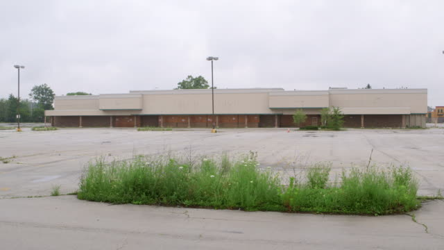 WS Abandoned shopping center with weeds growing in parking lot day