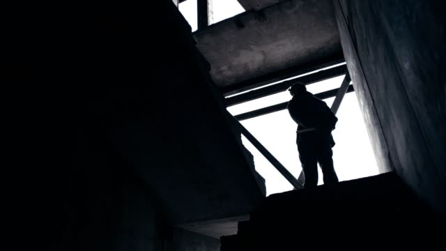 abandoned warehouse. polish martial law 1981. socialist militiaman on patrol - in silhouette stock videos & royalty-free footage