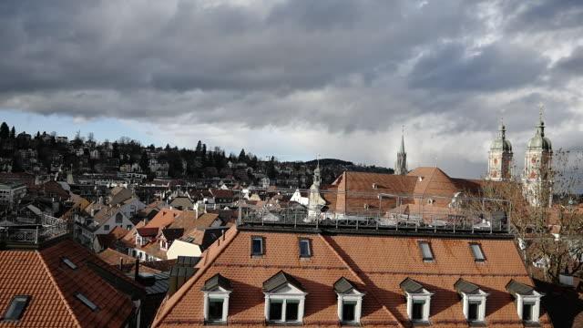 vidéos et rushes de abbey of st gallen and cityscape with cloudscape and sun - flèche clocher