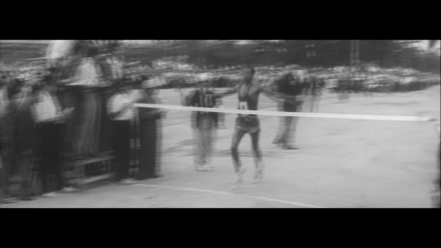 abebe bikila struggles against cars/47 athlete runners start in hamadera park abebe running abebe taking a drink traffic ever more entangled... - struggle stock videos and b-roll footage
