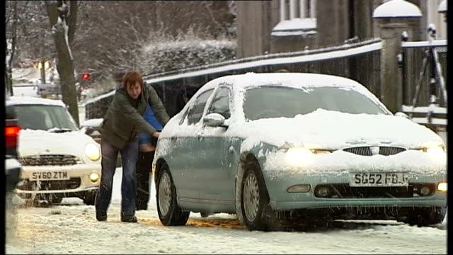 aberdeen whels of car spinning on slush covered road car being pushed along snowy road as more snow falls van sliding backwards on road highlands air... - slush stock videos and b-roll footage