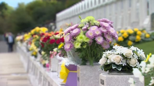 50th anniversary ext people visiting the aberfan memorial flowers laid alongside the mass grave where the victims of the disaster are buried memorial... - mass grave stock videos and b-roll footage