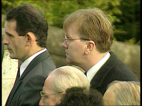 thirty years on anat wales aberfan mourners standing in line in front of the memorial to the children ms side mourners standing with heads bowed ms... - itv news at ten stock-videos und b-roll-filmmaterial