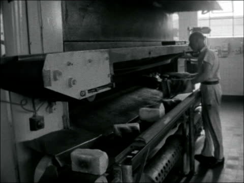 bakers interviewed ENGLAND London INT General view interior of multiple bakery / Dough from machine onto moving belt to the ovens / Baker puts dough...