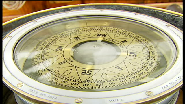 vídeos de stock, filmes e b-roll de 200th anniversary replica of the zong sails up river thames ext deck of the zong with crew busy ship's compass ship's wheel and bridge low angle shot... - compasso