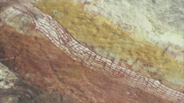 aboriginal art in the shape of a snake decorates a rock in oenpelli, australia. - rock object stock videos and b-roll footage