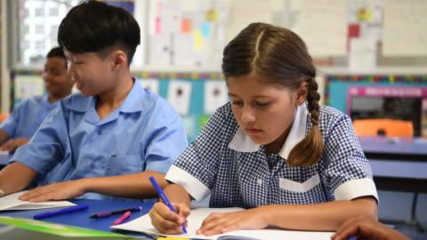 aboriginal australian school girl wearing checked dress writing in school book at desk - braided hair stock videos & royalty-free footage