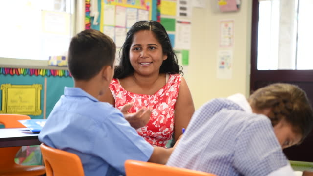 Aboriginal Australian schoolteacher smiling and helping young boy in the classroom